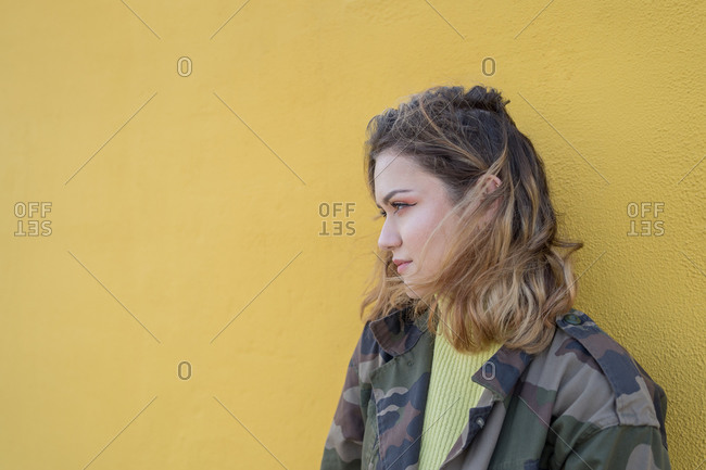 Young woman dressed in a military jacket leaning against a yellow wall with a distracted loo