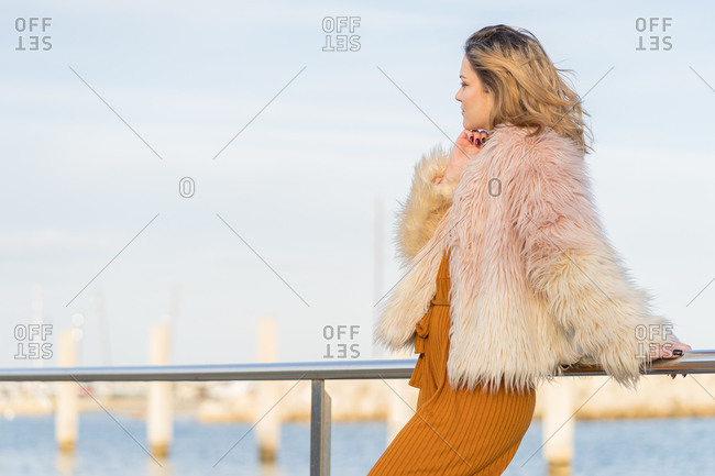 Young blonde woman with pink hair jacket leaning on the railing of the marina looking at the horizon