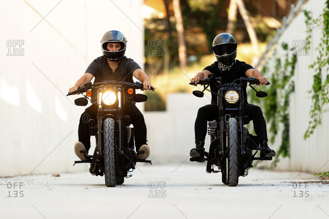 Two bikers riding on cafe racer motorcycles with lights on