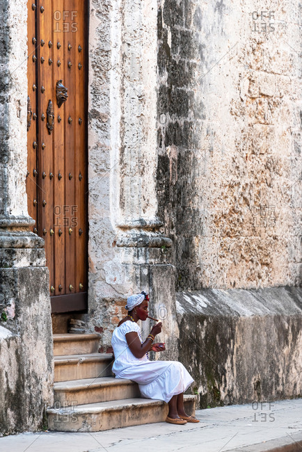 August 23, 2019: Cuban lady smoking a large cigar in La Havana. Havana, Cuba