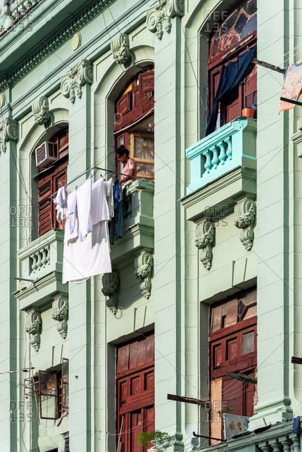 September 2, 2019: woman hanging the laundry on her balcony in Havana. Havana, Cuba