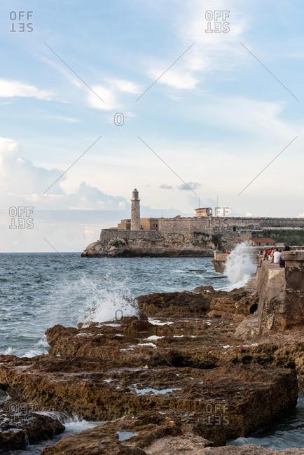 September 2, 2019: People sitting on The Malecon (coast road) in Havana. Havana, Cuba