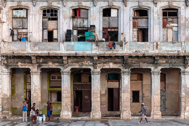September 3, 2019: People in front of a weathered facade of a residential building. Havana, Cuba