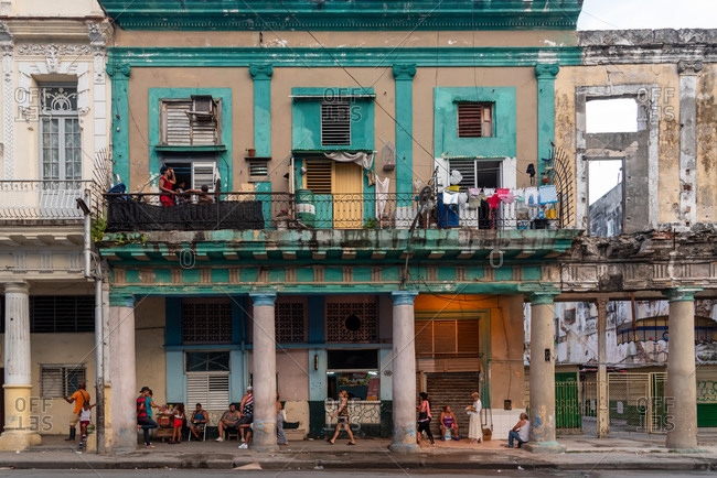 September 4, 2019: People in front of a weathered facade of a residential building. Havana, Cuba