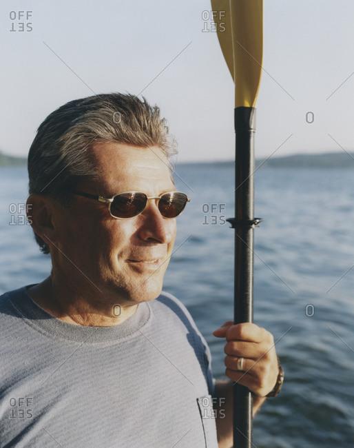 Portrait of middle aged man holding sea kayak paddle at dusk