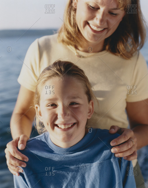 Portrait of happy mother and daughter outdoors at dusk,