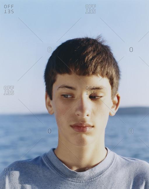 Portrait  of serious adolescent boy looking away, ocean in distance