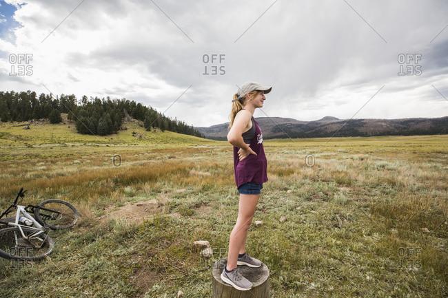 Teenage girl standing on stump