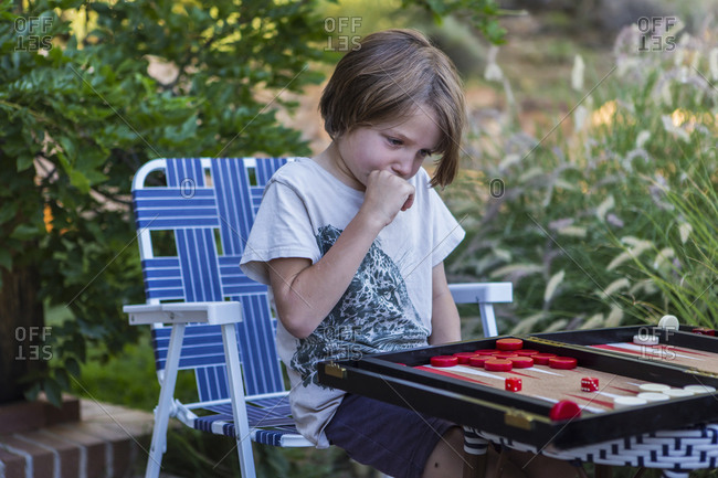 A young boy playing backgammon outdoors in a garden.