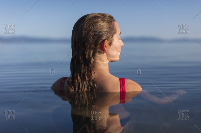 Teenage girl, head and shoulders above calm lake water at dawn