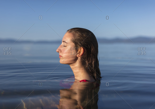 Teenage girl with eyes closed, head and shoulders above the calm waters of a lake at dawn