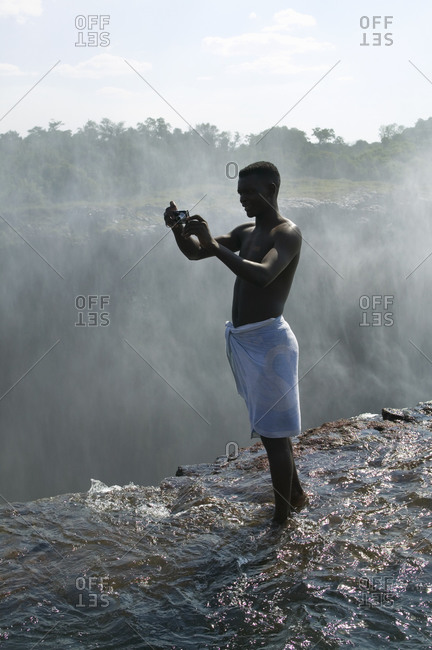 Zambia - October 8, 2020: Man standing on ledge of Victoria Falls, taking picture, Zambia.