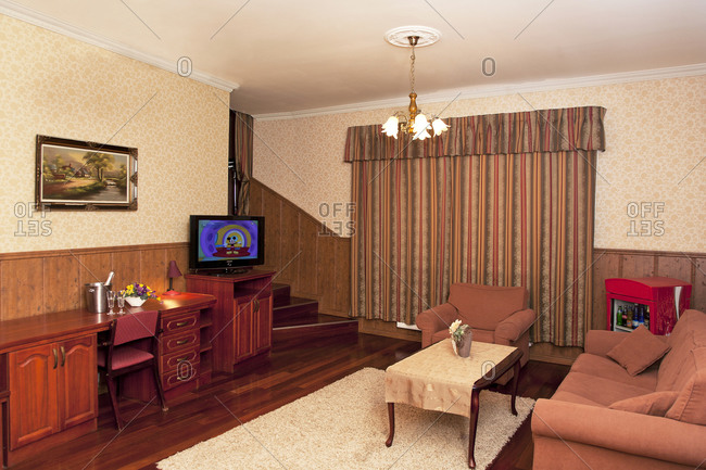 Estonia - September 22, 2020: A hotel with old fashioned retro styled rooms, and rustic objects, sofa and chairs and television.