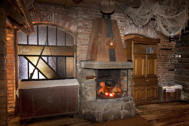 Estonia - September 22, 2020: A hotel with old fashioned retro styled rooms, and rustic objects, open lit fire with large stonework chimney and wooden floor