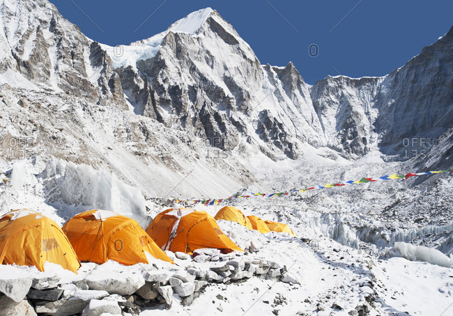 A group of orange tents at a climbers base camp in the Himalayas region.