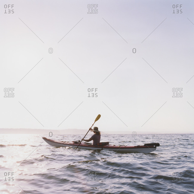 Middle aged woman sea kayaking at duskcan