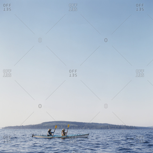 Middle aged man and woman sea kayaking on calm water
