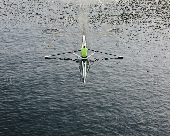 A single scull boat and rower on the water, view from above.