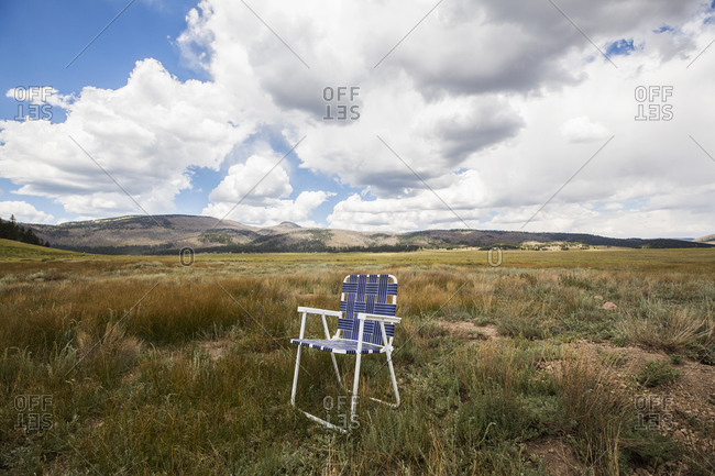 Single folding chair on a plain, mountains in the distance.