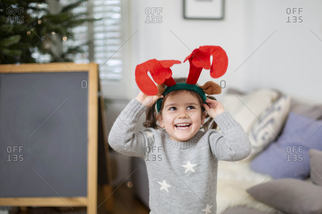 Smiling young girl wearing grey jumper putting on reindeer antler headband.