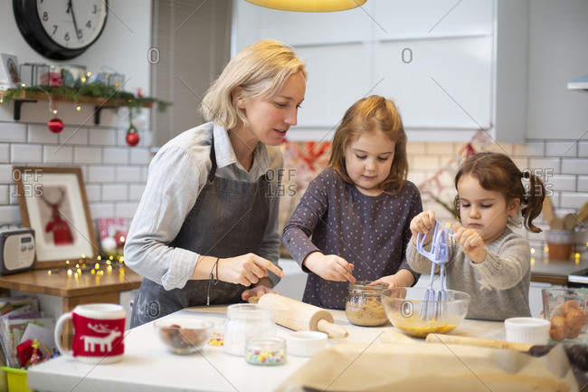Blond woman wearing blue apron and two girls standing in kitchen, baking Christmas cookies.