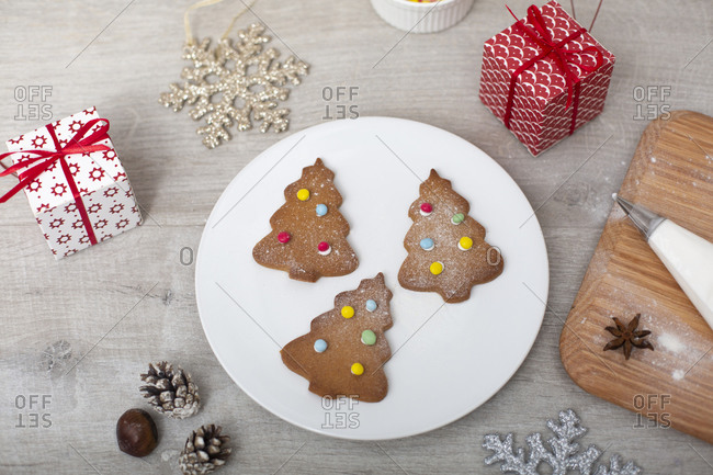 High angle close up of Christmas presents, decorations and Christmas Tree cookies on a white plate.