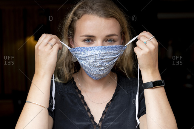 Portrait of young blond woman putting on blue face mask.