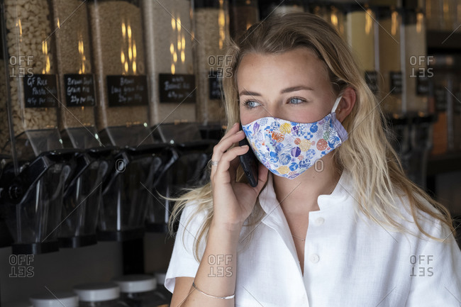 Portrait of young blond woman wearing face mask, standing in waste free wholefood store.
