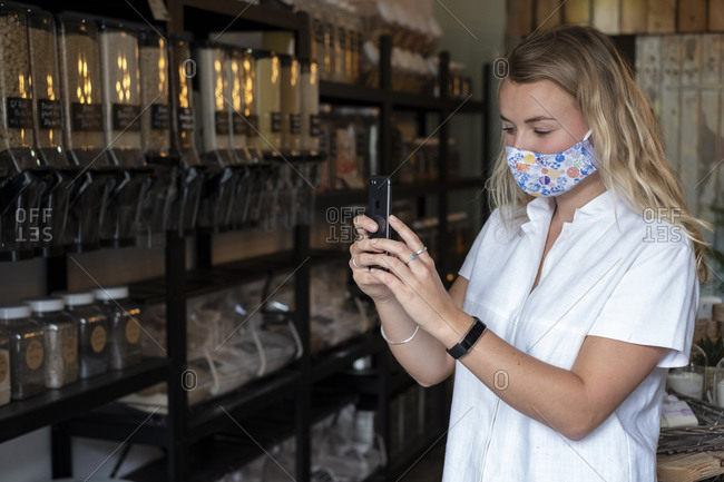 Woman wearing face mask in waste-free local store, using a mobile phone