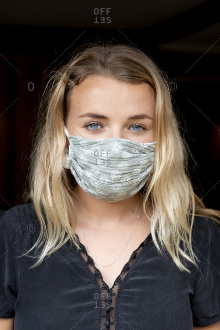 Portrait of young blond woman wearing blue face mask.