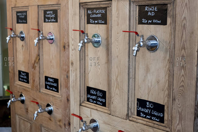 Close up of wooden dispensers for cleaning products in a waste free wholefood store.