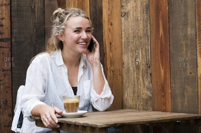 Young blond woman sitting alone in a cafe, using mobile phone, working remotely.