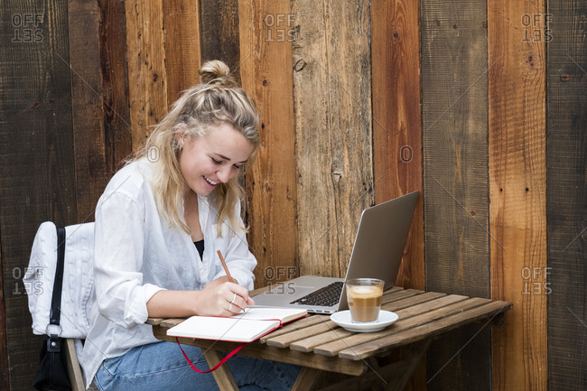 Young blond woman sitting alone at a cafe table with a laptop computer