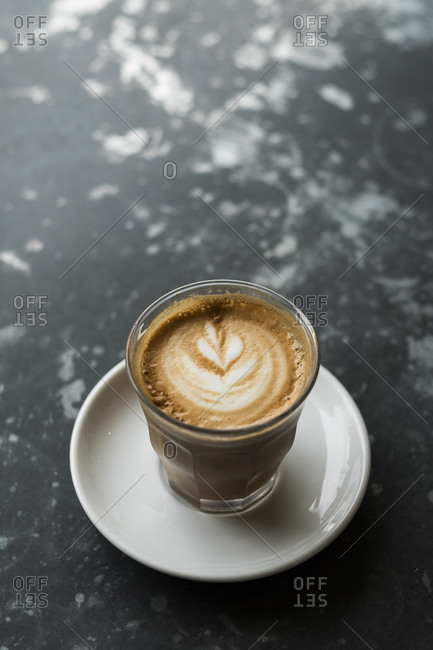 High angle close up of a cappuccino on a black marble table.