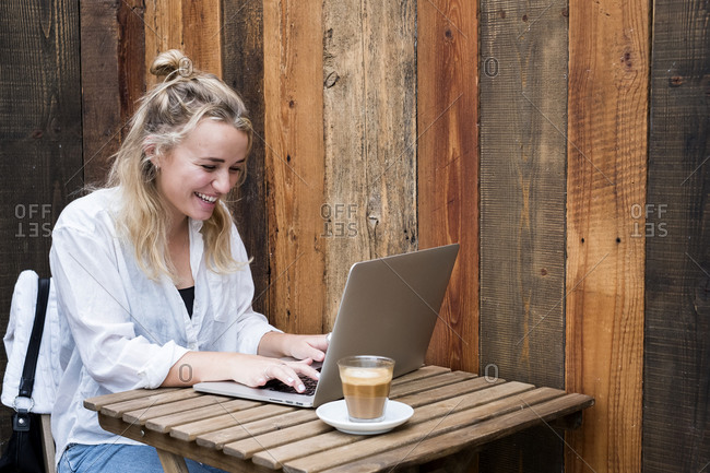 Young blond woman sitting alone at a cafe table with a laptop computer, working remotely.