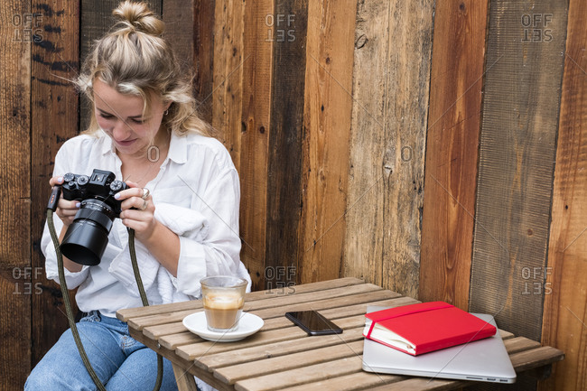 Young blond woman sitting alone at a cafe table, looking at digital camera display.