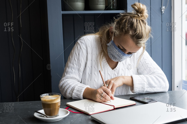 Woman wearing face mask sitting alone at a cafe table with a laptop computer, working remotely.