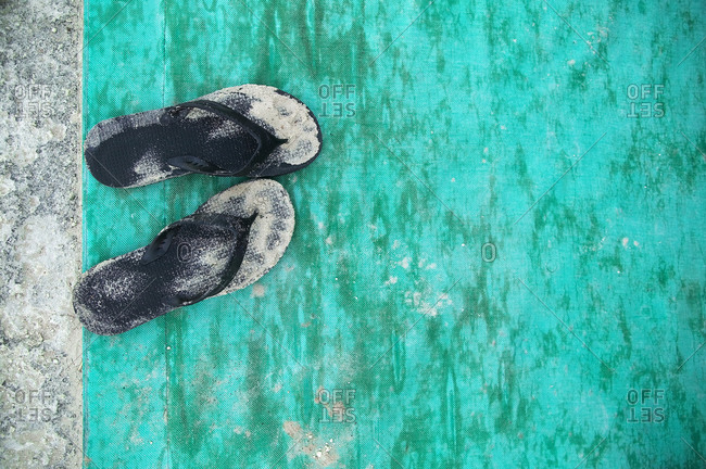 High angle close up of sandy black flip flops on turquoise floor mat.