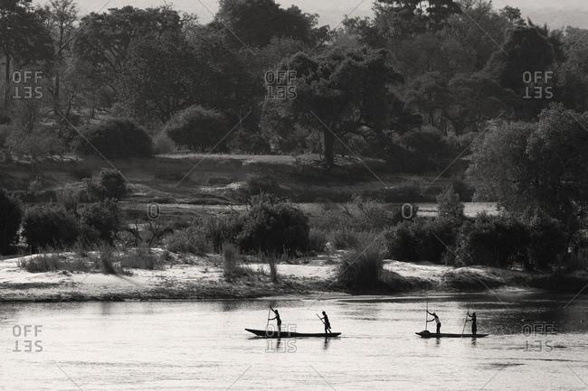 Locals going down the Zambezi River in traditional mokoro canoes, Zambia.