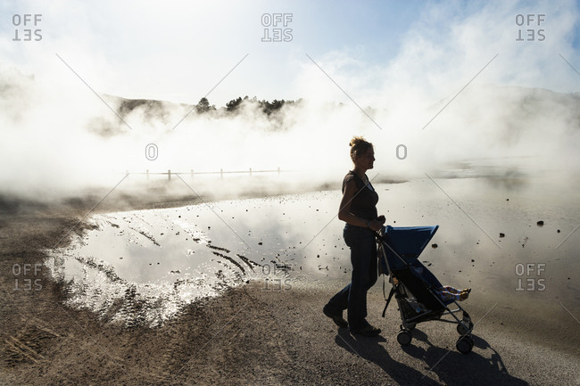 A woman and a child in a buggy in rising steam from thermal pools