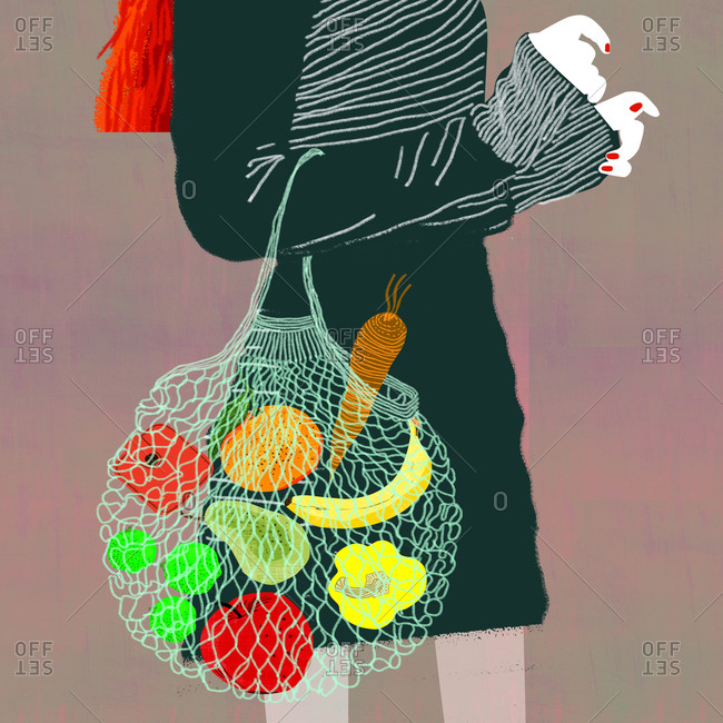 Side view of a slim woman with reusable shopping bag with vegetables and fruit