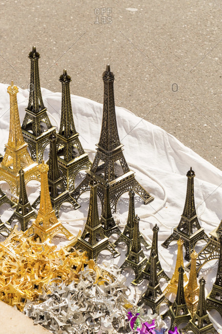 Eiffel tower souvenir miniatures in montmartre, paris spread out on a cloth on the ground for tourists