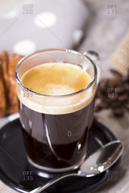 Delicious breakfast setting on gray wooden table with coffee in glass cup next to spoon and croissant on polka dotted napkin