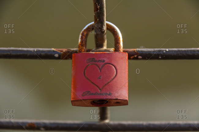 February 19, 2015: Colorful red love lock on a metal railing with an engraved heart icon on a bridge in strasbourg, alsace, france, close up view