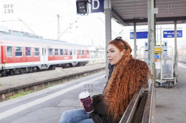 Thoughtful young woman with long red hair wears a coat and holds a coffee cup while waiting on a bench at a train station