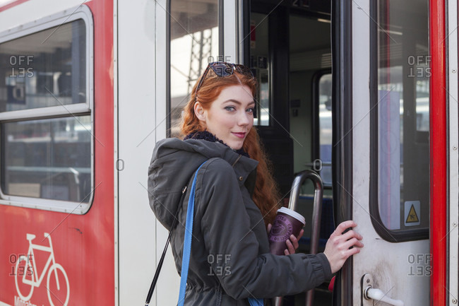 One confident young woman with long red hair wearing a coat steps onto a red train car labeled with the number two and displaying a bike decal