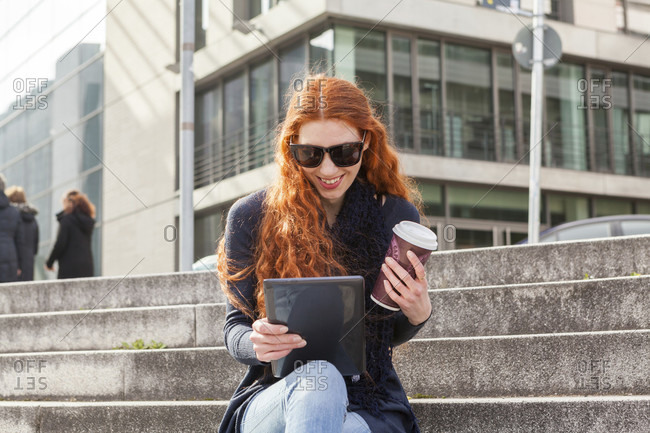 Trendy young red head wearing black boots and blue jeans seated on concrete steps smiles at her tablet on a sunny day