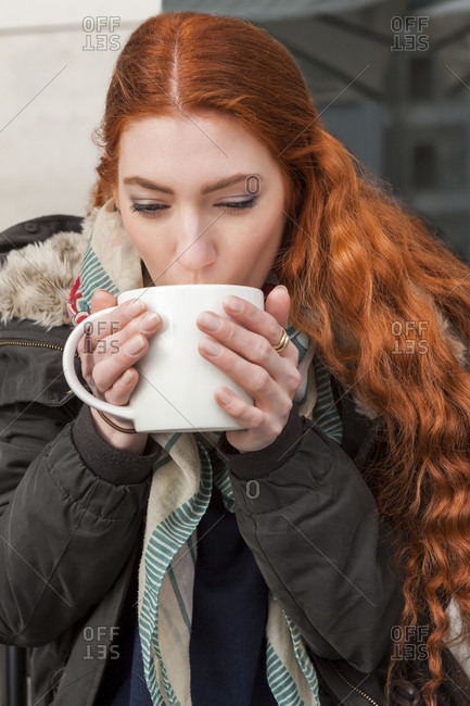 Happy red haired woman holding large white mug while seated at table outside in cool weather clothing