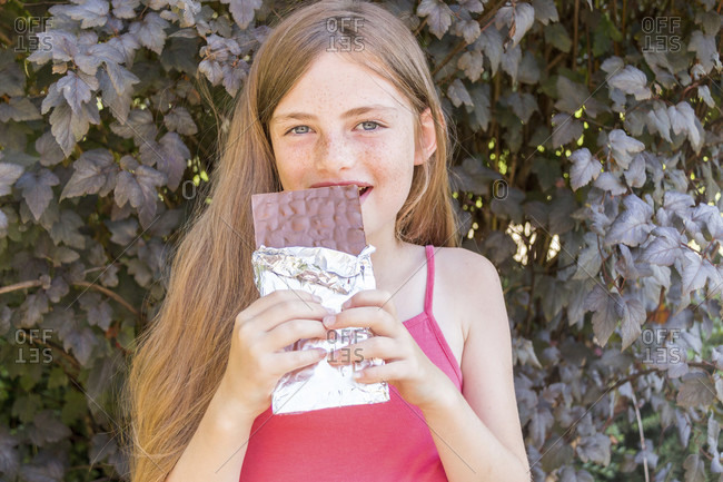 Adorable grinning freckled girl in long brown hair biting into large foil wrapped bar of chocolate while standing in front of ivy leaves