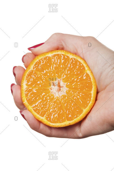 Woman with manicured red nails holding a halved fresh juicy orange in her hand in a close up view in a beauty and makeup concept